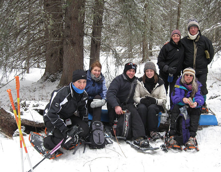 people on a snowshoeing outing sitting down